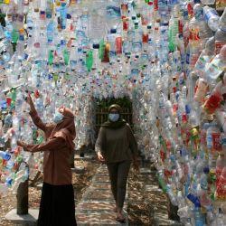 Personas caminan a través de una instalación construida con botellas de plástico durante una campaña ambiental, en Gresik, en Java Oriental, Indonesia. La instalación plástica fue construida con basura de plástico recogida de los ríos en Gresik y Surabaya.   Foto:Xinhua / Kurniawan