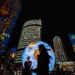 Un grupo de personas posa delante de un globo terráqueo iluminado mientras se proyectan diseños luminosos en un edificio de gran altura en la Potsdamer Platz como parte del Festival de las Luces que se celebra anualmente en Berlín.   Foto:John Macdougall / AFP