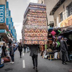 Un trabajador lleva colchones en la cabeza en el histórico barrio de Merkato durante los preparativos para la víspera del Año Nuevo etíope en Addis Abeba, Etiopía. | Foto:Amanuel Sileshi / AFP