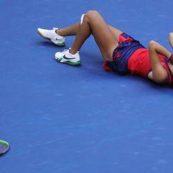 La británica Emma Raducanu se tumba en la pista mientras reacciona tras ganar su partido de la final individual femenina del US Open de Tenis 2021 contra la canadiense Leylah Fernández en el USTA Billie Jean King National Tennis Center de Nueva York.   Foto:Kena Betancur / AFP