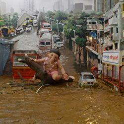 En esta fotografía se ve un diorama (modelo en miniatura) que representa al dios hindú Ganesha aferrado a la rama de un árbol en medio de una carretera inundada, creado por estudiantes de arte, durante las celebraciones para conmemorar el festival Ganesh Chaturthi en Mumbai.   Foto:Indranil Mukherjee / AFP