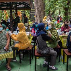 Trabajadores sanitarios inoculan a las personas una dosis de la vacuna Sinovac Covid-19 durante una vacunación masiva en un zoológico de Surabaya.   Foto:Juni Kriswanto / AFP