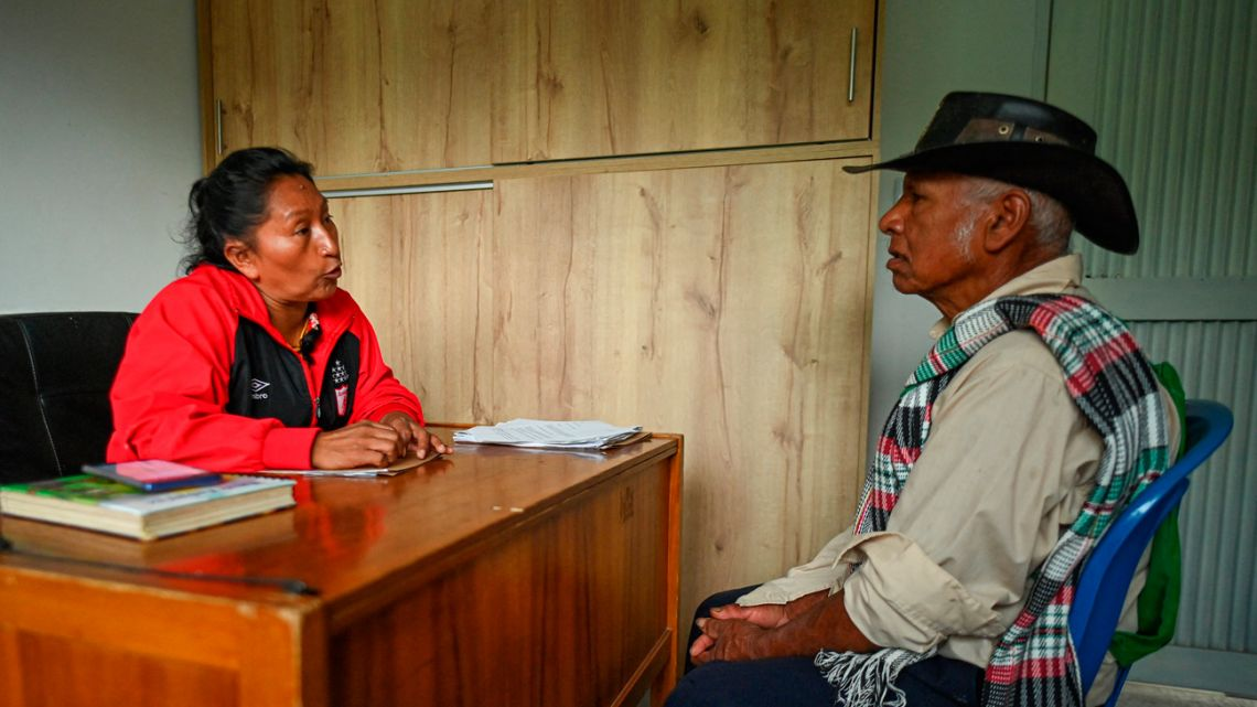 Colombian indigenous environmentalist Celia Umenza, 48, speaks with a man in Tacueyo, department of Cauca, Colombia on September 7, 2021. Death breathes on the nape of indigenous people who defend nature in Colombia, the deadliest country for environmentalists.
