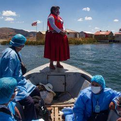 Trabajadores del Ministerio de Salud peruano acompañados por la ex alcaldesa de la isla de Uros, la gestora intercultural Rita Subana, son vistos durante un programa de inmunización de la población vulnerable que aún no ha recibido las vacunas contra el Covid-19 en la isla flotante de Uros en el lago Titicaca, Perú. | Foto:Carlos Mamani / AFP
