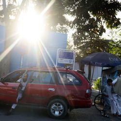 Un hombre se baja de su coche cerca de un puesto en una calle de Kabul. | Foto:Karim Sahib / AFP