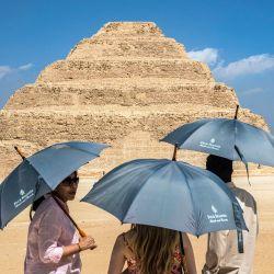 Los turistas se paran con paraguas cerca de la pirámide escalonada del faraón de la tercera dinastía del Antiguo Egipto Djoser (siglo XXVII a.C.) en la necrópolis de Saqqara, al sur de la capital de Egipto, El Cairo. | Foto:Khaled Desouki / AFP