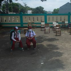 Estudiantes de primaria portan mascarillas mientras esperan para ser recogidos después de la escuela, en Tangerang del Sur, Indonesia. | Foto:Xinhua / Veri Sanovri