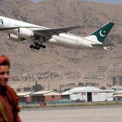 Un combatiente talibán monta guardia mientras un avión de Pakistan International Airlines, el primer vuelo comercial internacional que aterriza desde que los talibanes retomaron el poder el mes pasado, despega con pasajeros a bordo en el aeropuerto de Kabul.   Foto:Karim Sahib / AFP