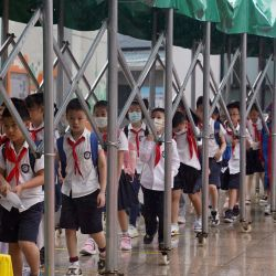 Estudiantes forman una fila bajo el cuidado de un toldo removible después de clases en una escuela primaria, en el distrito de Huangpu, en Shanghai, en el este de China.   Foto:Xinhua / Liu Yingi