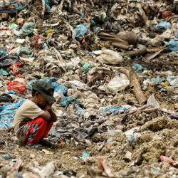 El hijo de un recolector de basura descansa mientras su padre (no se ve en la foto) busca artículos que puedan ser revendidos, en un basurero de Alue Liem en Lhokseumawe.   Foto:Azwar Ipank / AFP