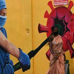Unas mujeres pasan por delante de un mural de concienciación sobre el coronavirus Covid-19 a lo largo de la carretera en Chennai.   Foto:Arun Sankar / AFP