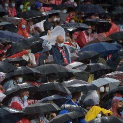Los espectadores se cubren de la lluvia durante el partido de fútbol de la primera ronda del grupo G de la UEFA Champions League entre el Sevilla y el Salzburgo en el estadio Ramón Sánchez Pizjuán de Sevilla.   Foto:Cristina Quicler / AFP