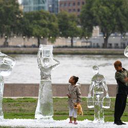 Unos niños posan junto a unas esculturas de hielo que representan a personas recogiendo agua realizadas por la organización benéfica Water Aid para mostrar la fragilidad del agua y la amenaza que supone el cambio climático en Londres. | Foto:Daniel Leal-Olivas / AFP