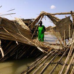 Refugiados sudsudaneses intentan reparar su cabaña en las aguas inundadas del Nilo Blanco en un campo de refugiados que se inundó tras las fuertes lluvias cerca de al-Qanaa en el sur de Sudán. | Foto:Ashraf Shazly / AFP