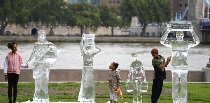 Unos niños posan junto a unas esculturas de hielo que representan a personas recogiendo agua realizadas por la organización benéfica Water Aid para mostrar la fragilidad del agua y la amenaza que supone el cambio climático en Londres.
