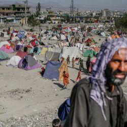 Un hombre pasa por delante de un campamento de desplazados internos en Kabul.   Foto:Bulent Kilic / AFP