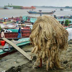 Un trabajador lleva yute para cargarlo en un barco en un mercado rural en Munshigonj.   Foto:Munir Uz Zaman / AFP