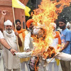 Los agricultores gritan consignas mientras queman una efigie del primer ministro de la India, Narendra Modi, durante una protesta contra las reformas agrícolas del gobierno central, en Amritsar.   Foto:Narinder Nanu / AFP