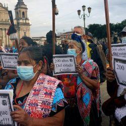 Indígenas mayas sostienen pancartas durante una protesta contra el Bicentenario de la Independencia de Guatemala en la que también exigieron la renuncia del presidente guatemalteco Alejandro Giammattei y de la fiscal general de Guatemala Consuelo Porras en la Plaza de la Constitución en Ciudad de Guatemala.   Foto:Johan Ordonez / AFP
