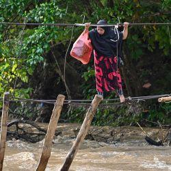 Una mujer cruza un río utilizando los restos de un puente, arrastrado durante las inundaciones del año anterior, en la aldea de Malela en la Regencia de Luwu.   Foto:Hariandi Hafid / AFP