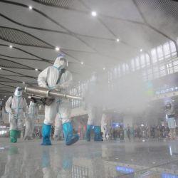 Los bomberos rocían desinfectante en la estación de tren de Yangzhou Este en Yangzhou, en la provincia oriental china de Jiangsu.   Foto:STR / AFP