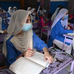Alumnos con mascarillas asisten a una clase en una escuela de Lahore, después de que el gobierno reabriera los institutos educativos que estaban cerrados como medida preventiva para frenar la propagación del coronavirus Covid-19.   Foto:Arif Ali / AFP