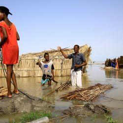 Refugiados sursudaneses intentan reparar su cabaña en las aguas inundadas del Nilo Blanco en un campo de refugiados que se inundó tras las fuertes lluvias cerca de al-Qanaa en el sur de Sudán.   Foto:Ashraf Shazly / AFP