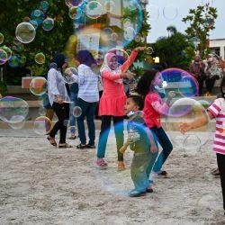 Residentes locales juegan con burbujas en Pantai Cenang, en Langkawi, un día antes de que la isla de vacaciones de Malasia se reabra a los turistas nacionales tras los cierres debidos a las restricciones para detener la propagación del coronavirus Covid-19.   Foto:Mohd Rasfan / AFP