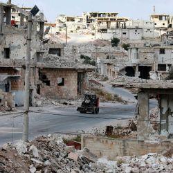 Una imagen tomada durante un recorrido organizado por el Ministerio de Información sirio muestra una excavadora en medio de la destrucción en el distrito de Daraa al-Balad de la ciudad meridional de Siria. - La mitad de Daraa, en manos de la oposición, volvió al control del Estado en virtud de un reciente acuerdo de rendición, según el cual, los combatientes que aceptan la tregua han sido invitados a entregar sus armas y firmar para quedarse en la ciudad en el marco de un llamado proceso de reconciliación.   Foto:Louai Beshara / AFP