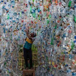 Un activista indonesio de ECOTON (observación ecológica y conservación de humedales) prepara una instalación hecha con plástico usado, incluidas 4.444 botellas, recogidas del río en Gresik, para concienciar a la población sobre los residuos de plástico en los ríos y océanos.   Foto:Juni Kriswanto / AFP