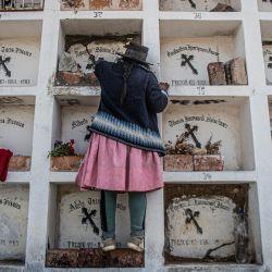 Un familiar limpia una de las 69 tumbas de personas asesinadas el 3 de abril de 1983 en la localidad de Santiago Lucanamarca, en Ayacucho, al sur de Perú. - La noche del 3 de abril de 1983, una columna de 60 guerrilleros armados con machetes, hachas, cuchillos y armas de fuego entraron en esta empobrecida comunidad campesina y convocaron a la gente a la plaza central donde mataron a 69 lugareños, recuerdan los testigos.   Foto:Ernesto Benavides / AFP