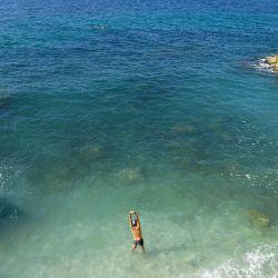 Un hombre se estira antes de ir a nadar bajo un cielo azul en el mar Mediterráneo en Marsella, sur de Francia.   Foto:Nicolas Tucat / AFP