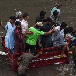 Los hombres viajan en un vehículo de tres ruedas a través de una calle inundada después de una fuerte lluvia en Lahor. | Foto:AFP