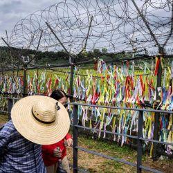 Los visitantes pasan por una valla adornada con cintas con mensajes escritos en ellos, en el 'parque de la paz' de Imjingak, cerca de la Zona Desmilitarizada (DMZ) que separa Corea del Norte y Corea del Sur.  | Foto:AFP