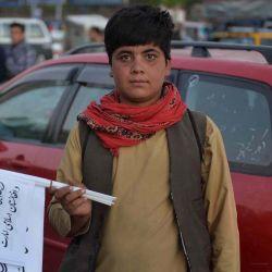 Un niño que vende banderas talibanes posa para una foto mientras espera a los clientes a lo largo de una carretera en Herat.  | Foto:AFP