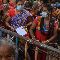 Las personas se reúnen para protestar frente al hospital del distrito administrado por el gobierno en Siliguri, afirman que no han sido vacunadas incluso después de acampar durante la noche en las instalaciones del hospital. | Foto:AFP