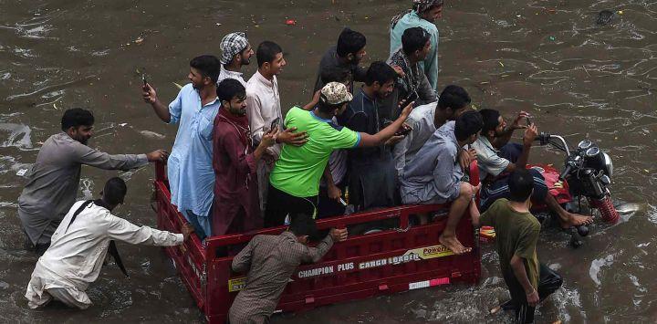 Los hombres viajan en un vehículo de tres ruedas a través de una calle inundada después de una fuerte lluvia en Lahor.