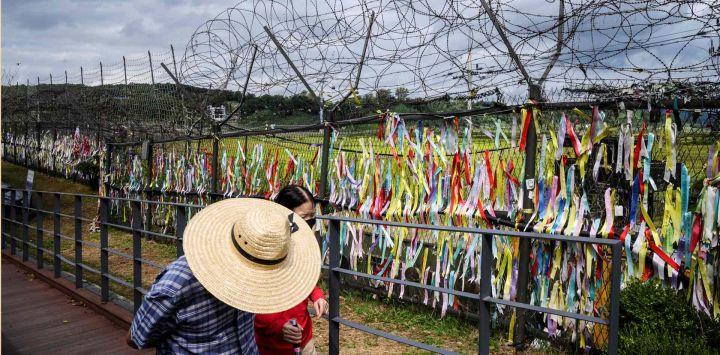 Los visitantes pasan por una valla adornada con cintas con mensajes escritos en ellos, en el 'parque de la paz' de Imjingak, cerca de la Zona Desmilitarizada (DMZ) que separa Corea del Norte y Corea del Sur.