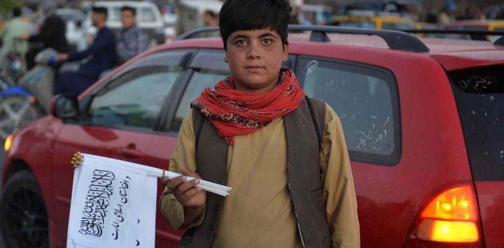 Un niño que vende banderas talibanes posa para una foto mientras espera a los clientes a lo largo de una carretera en Herat.