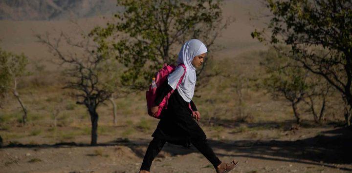 Los niños afganos caminan por un sendero de camino a su escuela en las afueras de Herat.