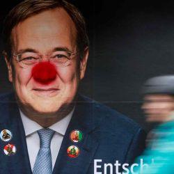 Un ciclista pasa junto a un cartel electoral del líder del partido conservador Unión Demócrata Cristiana (CDU) de Alemania y candidato a canciller ArminLaschet rociado con una nariz de payaso en Berlín.  | Foto:AFP