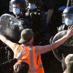 La policía confronta a trabajadores de la construcción y manifestantes con gases lacrimógenos en los escalones del Santuario del Recuerdo durante una protesta contra las regulaciones de Covid-19 en Melbourne.  | Foto:AFP