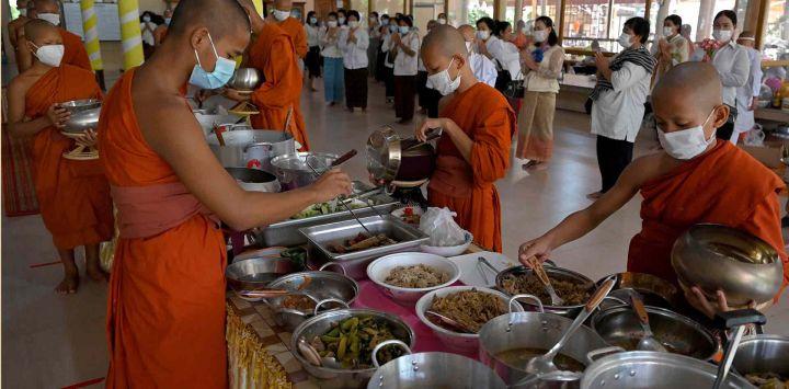 Los monjes budistas recolectan comida para el almuerzo durante el festival Pchum Ben (Festival de la Muerte) en una pagoda en Phnom Penh.
