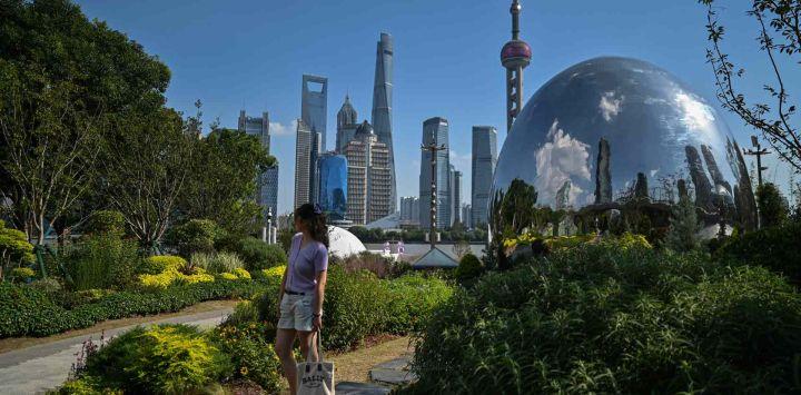 Una mujer posa para una foto para su familia en un parque mientras se ve el distrito financiero de Lujiazui (atrás) en Shanghai.