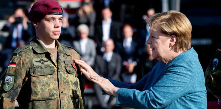 La canciller alemana, AngelaMerkel, premia a un soldado durante un pase de lista militar de la operación de evacuación militar (MilEvakOp), en Seedorf, en el norte de Alemania.