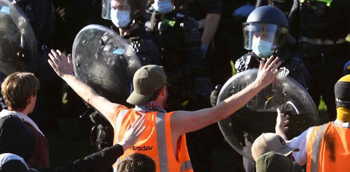 La policía confronta a trabajadores de la construcción y manifestantes con gases lacrimógenos en los escalones del Santuario del Recuerdo durante una protesta contra las regulaciones de Covid-19 en Melbourne.