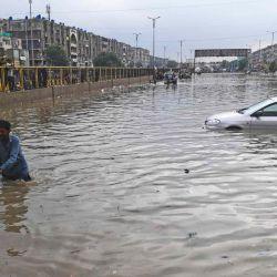 Un hombre empuja su motocicleta por una calle inundada después de una fuerte lluvia en Karachi.  | Foto:AFP