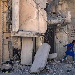 Un estudiante sirio camina hacia la escuela pasando por edificios dañados en la ciudad norteña de Raqqa. | Foto:AFP