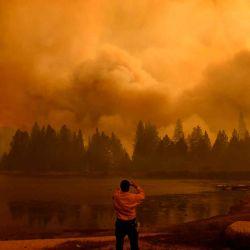 Un oficial de información pública toma fotografías mientras las llamas y el humo se elevan en el aire mientras el fuego arde durante el WindyFire en el Bosque Nacional Sequoia cerca de Johnsondale, California. | Foto:AFP
