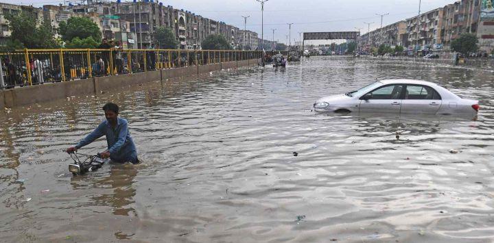 Un hombre empuja su motocicleta por una calle inundada después de una fuerte lluvia en Karachi.